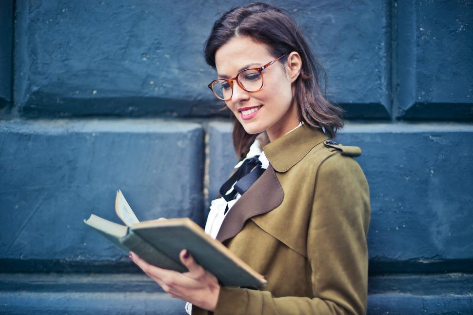Download Free Stock HD Photo of Young Woman In Suede Pea coat Reading a Book Online