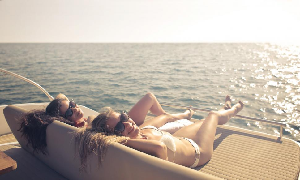 Download Free Stock HD Photo of Two Young Woman In White Bikini sunbathing on luxury yacht Online