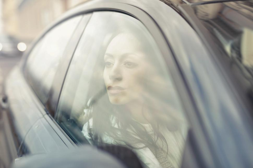 Download Free Stock HD Photo of A young woman driving a car looks outside to her right Online