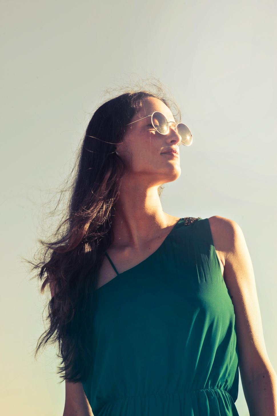 Download Free Stock HD Photo of A young brunette woman with glasses looks towards the sun Online
