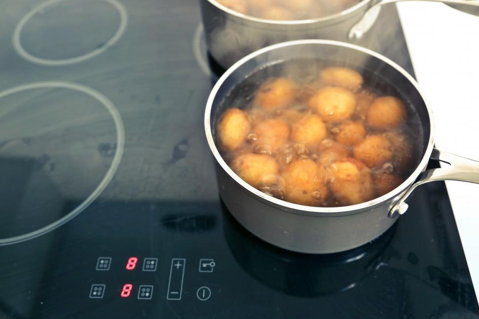 Download Free Stock HD Photo of Potatoes boiling in the pots on induction hob Online