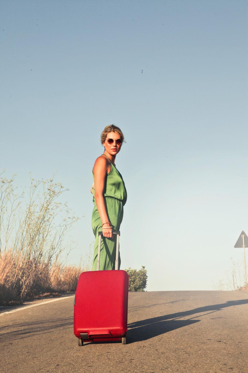 Download Free Stock HD Photo of A young blonde woman posing with red luggage trolley Bag Online