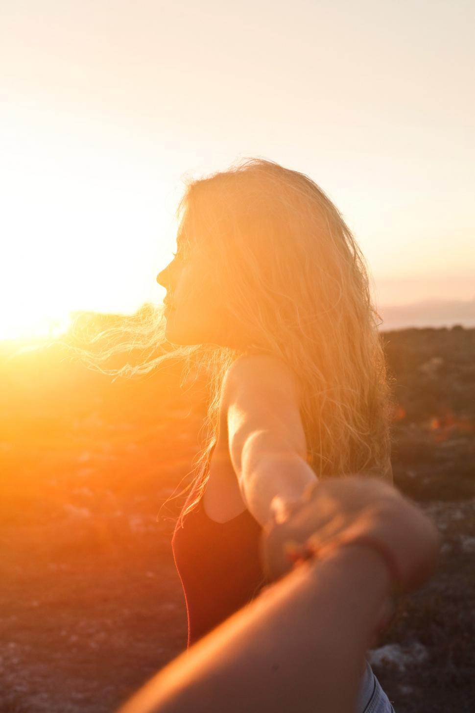 Download Free Stock HD Photo of A young blonde woman looking at the sunset Online