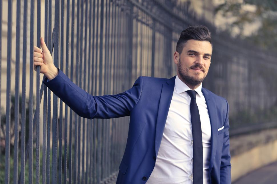 Download Free Stock HD Photo of A bearded caucasian man in formals standing against metal railin Online