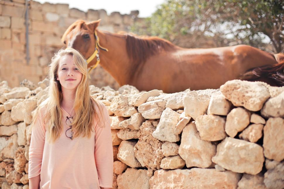 Download Free Stock HD Photo of A teenage blonde girl standing outside a horse ranch Online