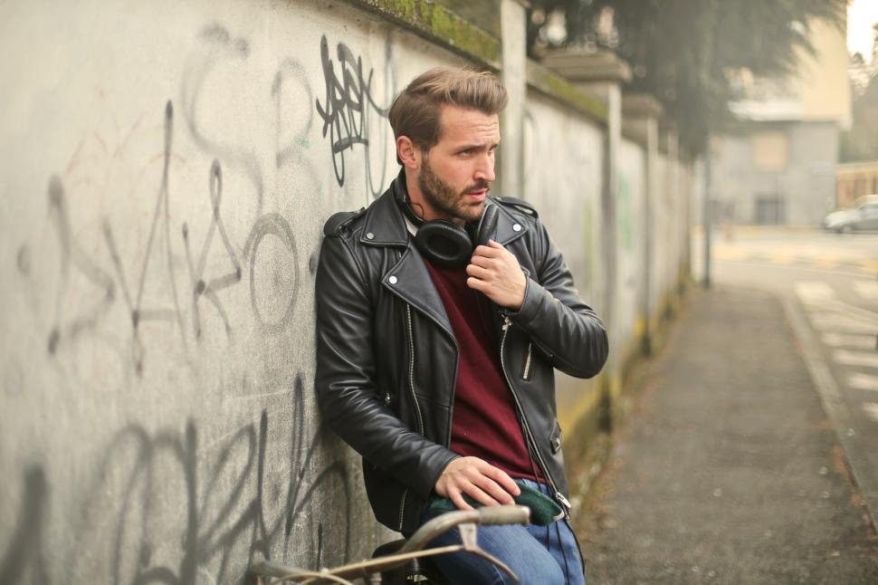Download Free Stock HD Photo of A young bearded caucasian man sitting against a wall on a bicycl Online