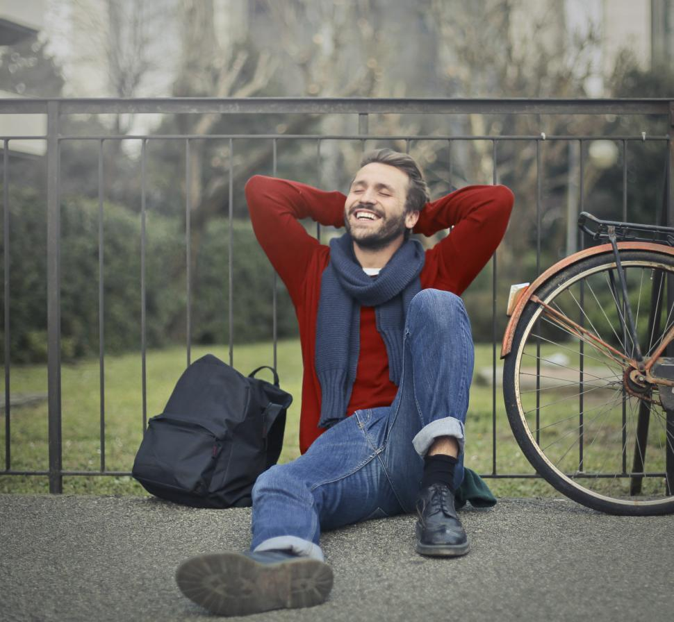 Download Free Stock HD Photo of A young bearded caucasian man sitting against metal railings wit Online