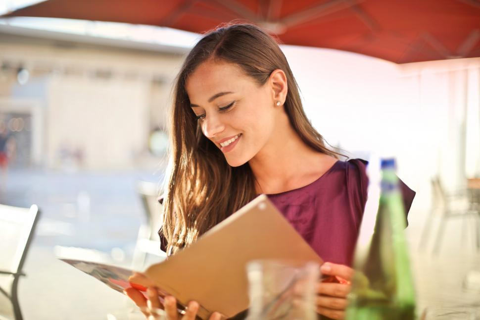 Download Free Stock HD Photo of A young blonde woman looking at a restaurant menu Online