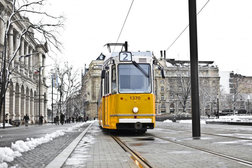 Download Free Stock HD Photo of A yellow tram on a snowy road Online