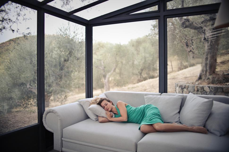 Download Free Stock HD Photo of A young blonde woman sleeping on the couch in a glass house Online