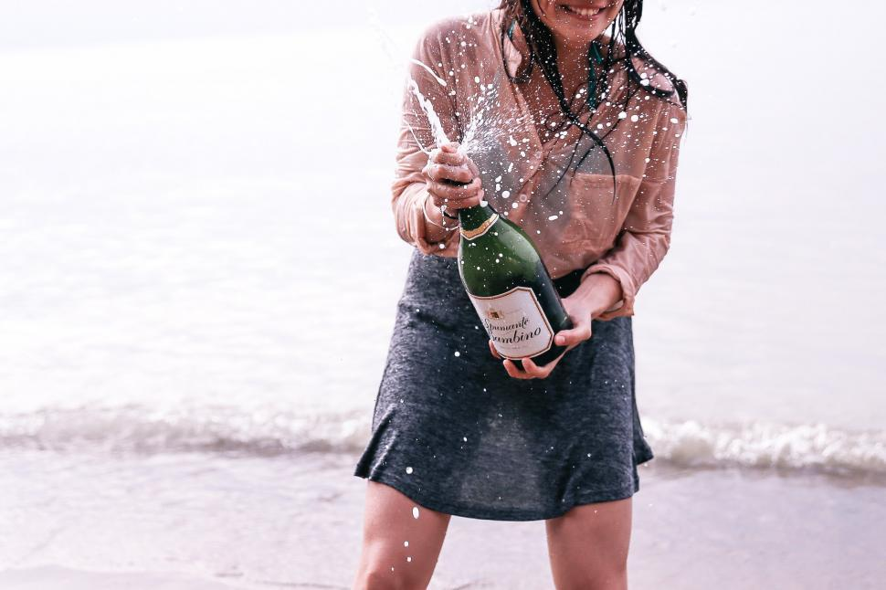 Download Free Stock HD Photo of A young caucasian woman splashing champagne on the beach Online