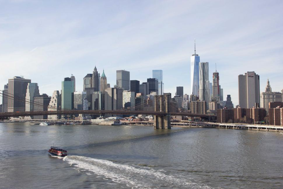 Download Free Stock HD Photo of A boat passes under Brooklyn bridge Online
