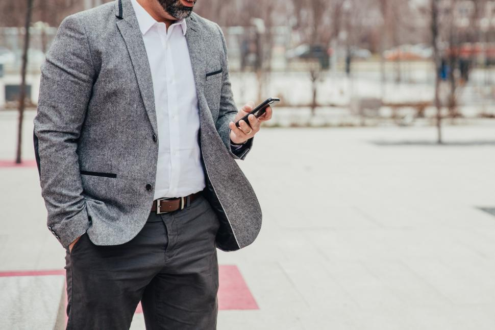 Download Free Stock HD Photo of A businessman looks at mobile phone outdoors Online
