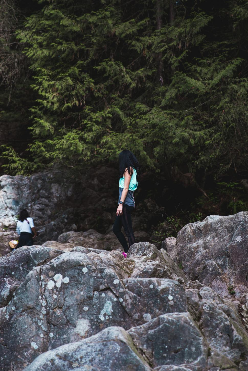 Download Free Stock HD Photo of A young female hiker standing on a rock Online
