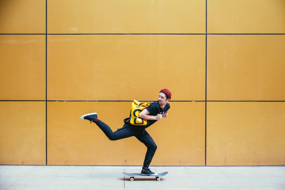 Download Free Stock HD Photo of A young caucasian skateboarder rides past a street wall Online