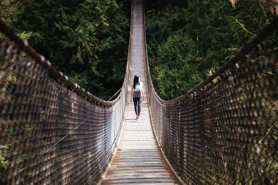 Download Free Stock HD Photo of A young Asian woman walking on the bridge Online