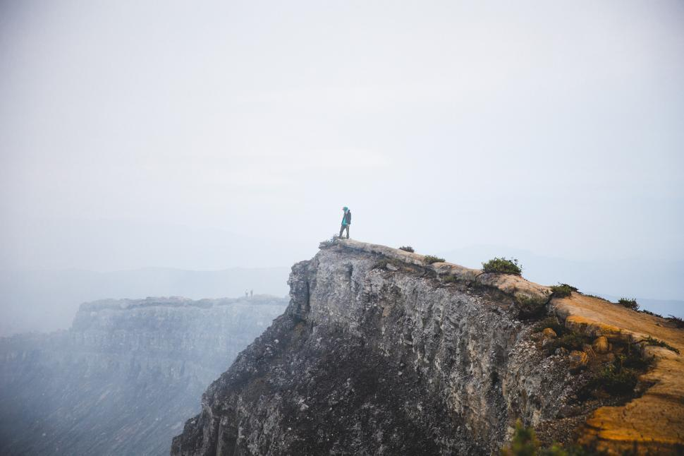 Download Free Stock HD Photo of A young hiker peaks over a rocky edge Online