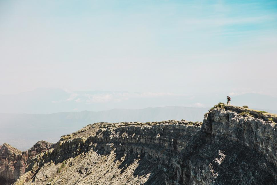 Download Free Stock HD Photo of A hiker with camera on rocky edge Online