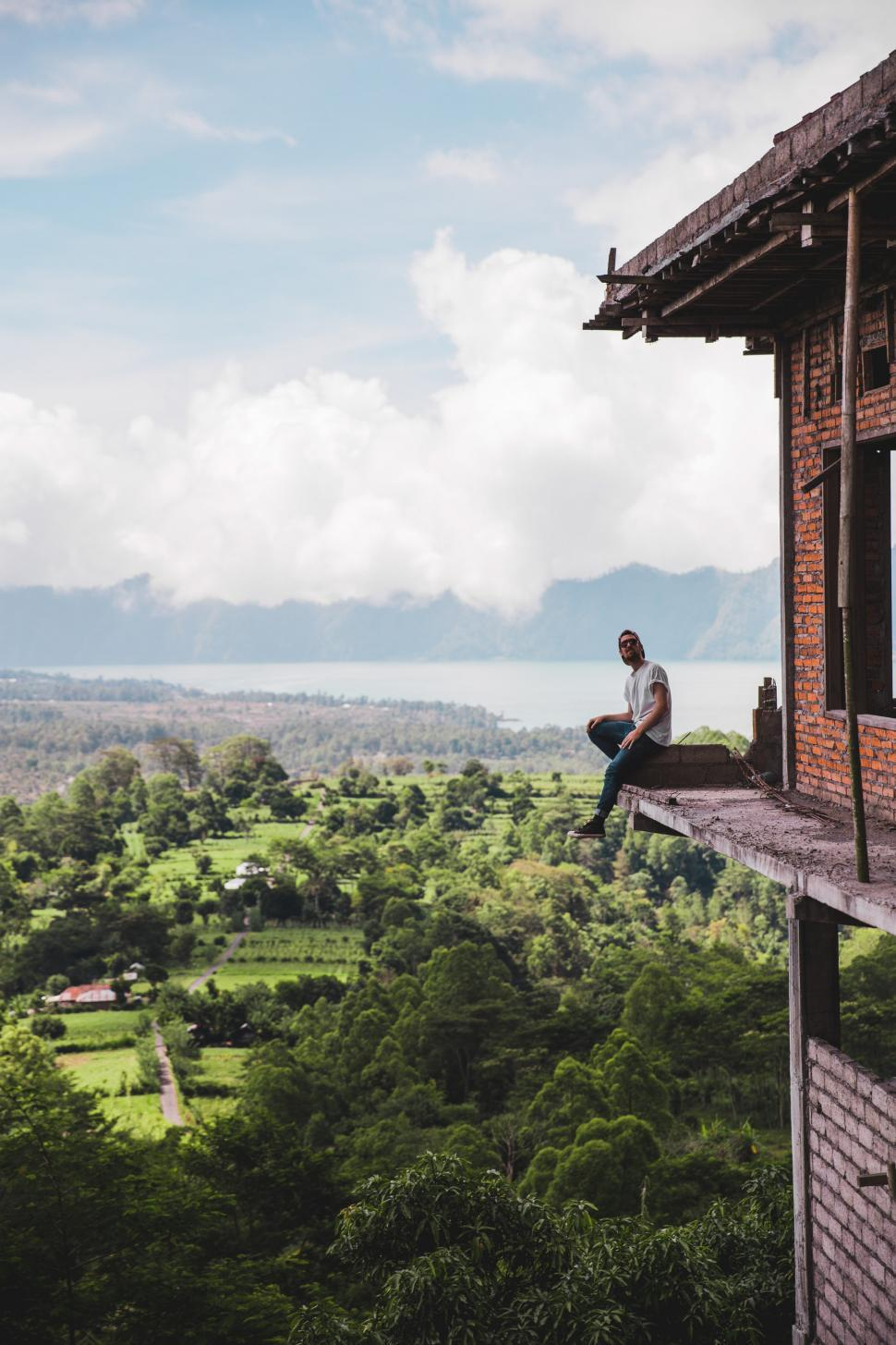 Download Free Stock HD Photo of A young Caucasian man sitting on the edge of a balcony Online