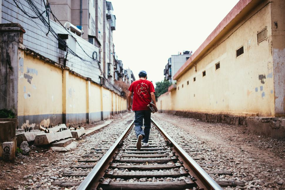 Download Free Stock HD Photo of A young skateboarder walking on train tracks Online