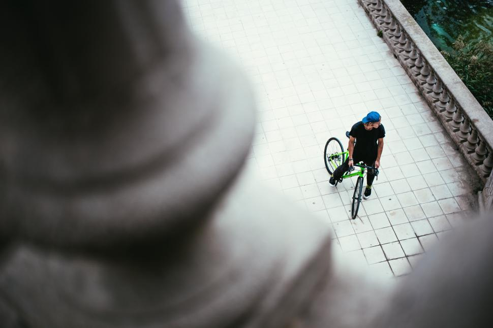 Download Free Stock HD Photo of A young Caucasian male cyclist halts on the street Online