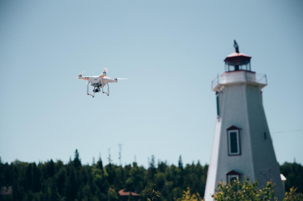 Download Free Stock HD Photo of A drone in flight near a lighthouse Online