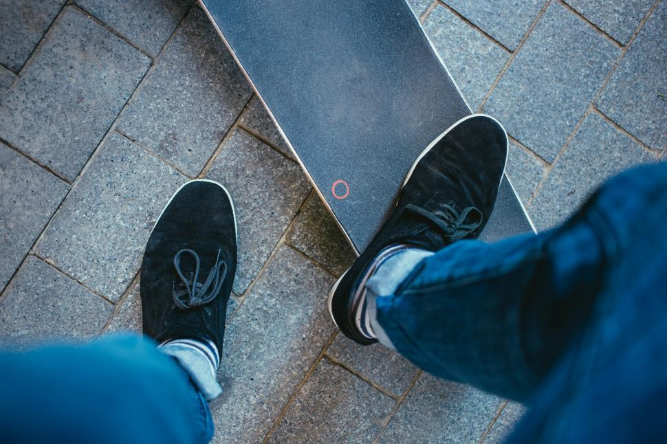 Download Free Stock HD Photo of A skater stepping on a skateboard deck Online