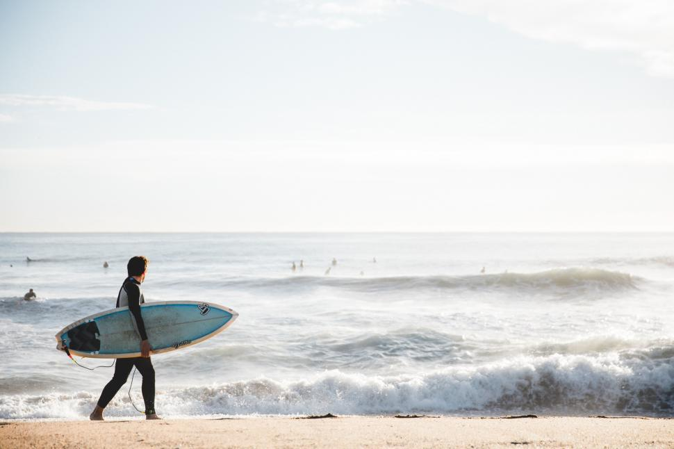 Download Free Stock HD Photo of A young Caucasian surfer carrying surfboard on the beach Online