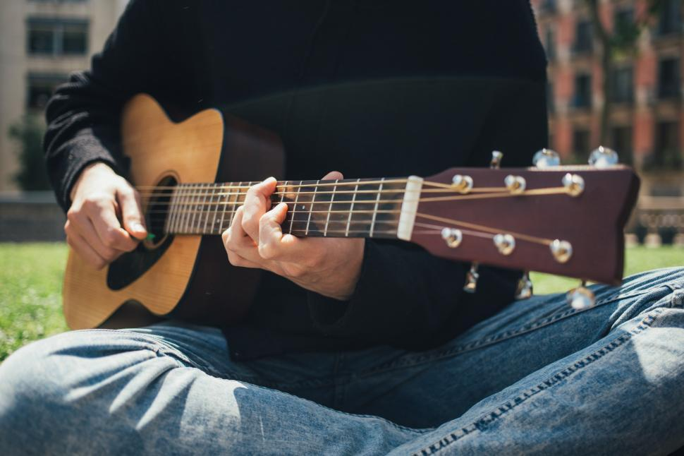 Download Free Stock HD Photo of A young man playing guitar in the park Online