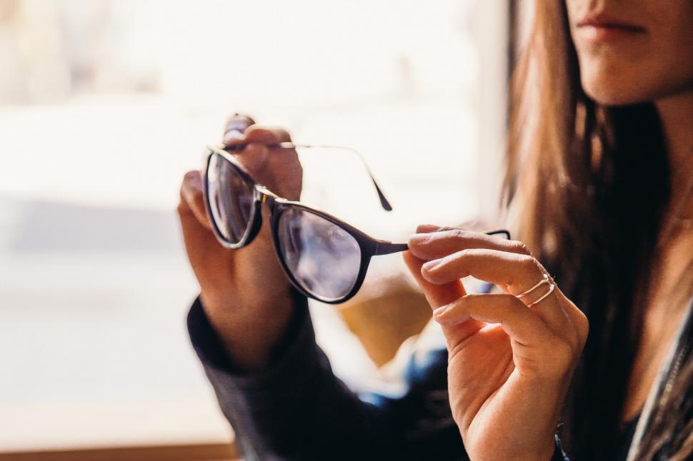 Download Free Stock HD Photo of A young caucasian woman trying on sunglasses Online