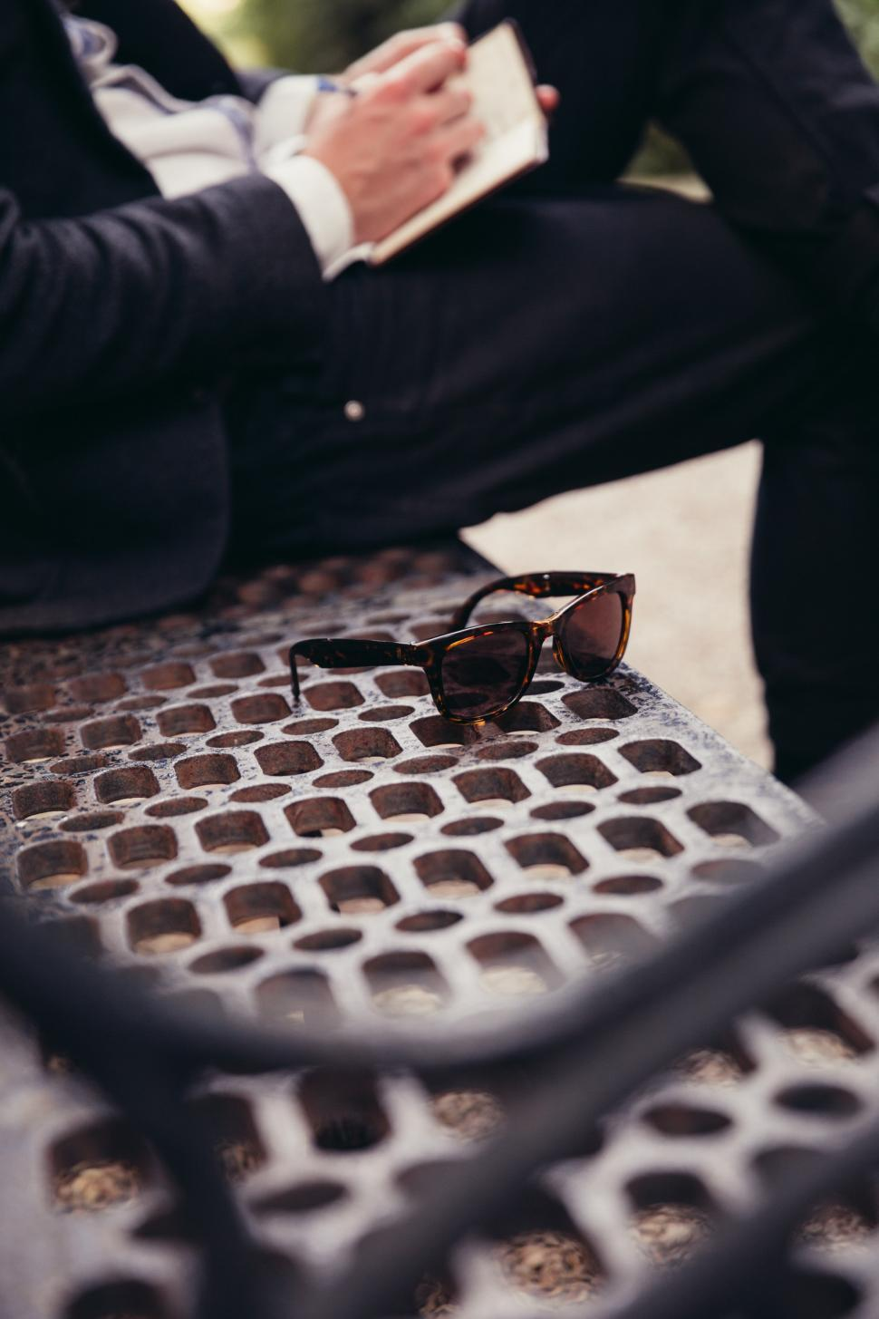 Download Free Stock HD Photo of A caucasian man writing and sunglasses kept on a park bench Online
