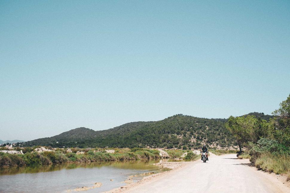 Download Free Stock HD Photo of A young motorcyclist on a hilly road Online