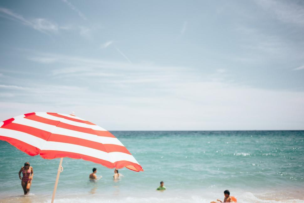Download Free Stock HD Photo of A beach umbrella and people swimming Online
