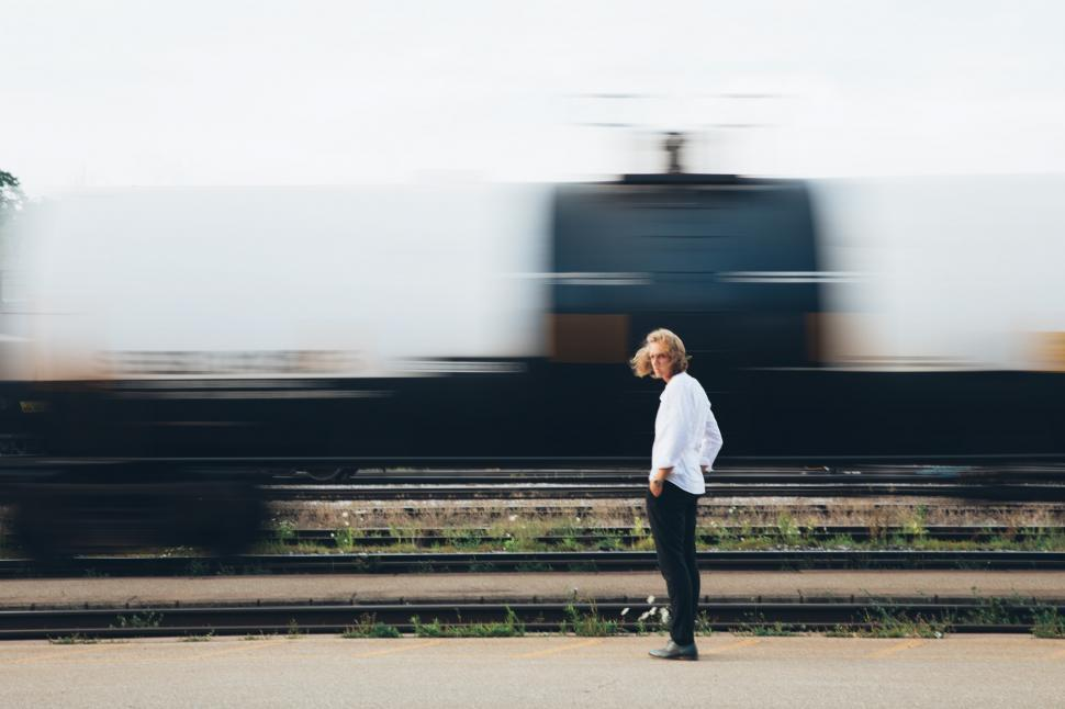 Download Free Stock HD Photo of A young caucasian man standing near passing train Online