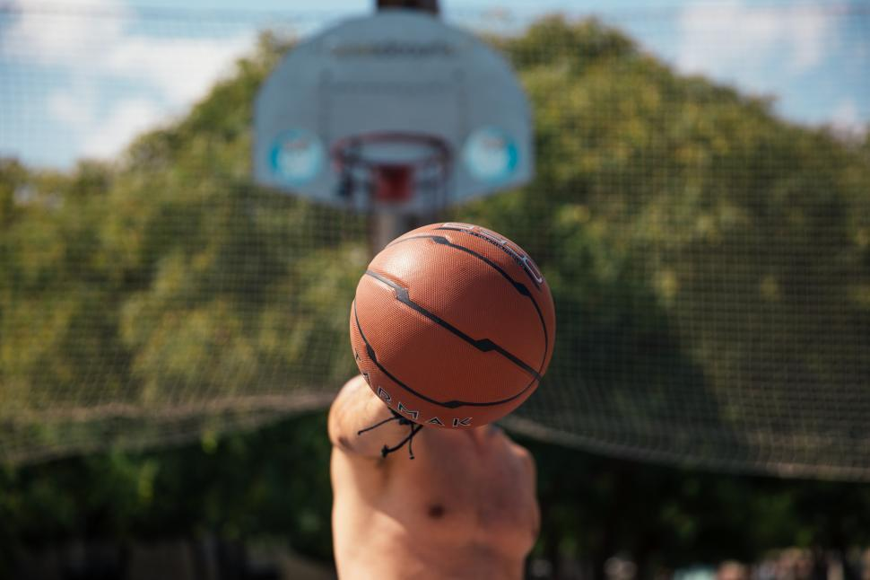 Download Free Stock HD Photo of A young man holding a basketball in his hand Online