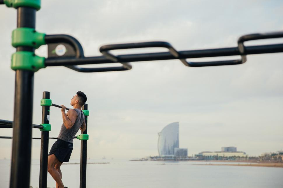 Download Free Stock HD Photo of A young Asian man doing chin-up exercise Online