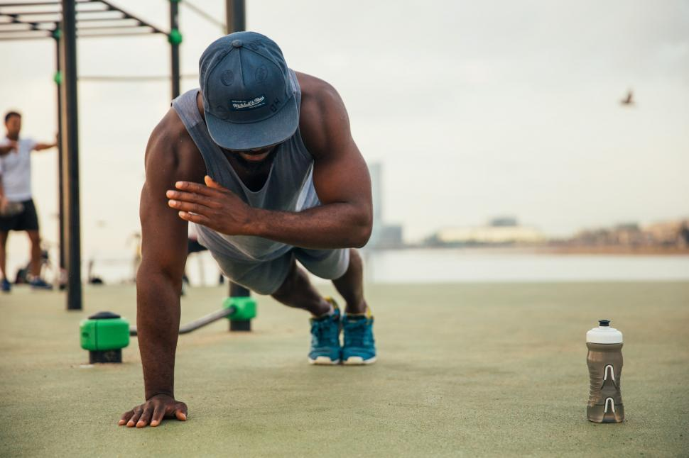 Download Free Stock HD Photo of One armed push-up exercise by a young african man Online