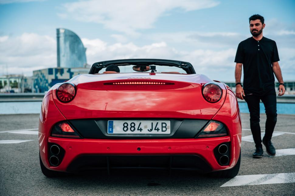 Download Free Stock HD Photo of A young man standing beside a red convertible sports car Online