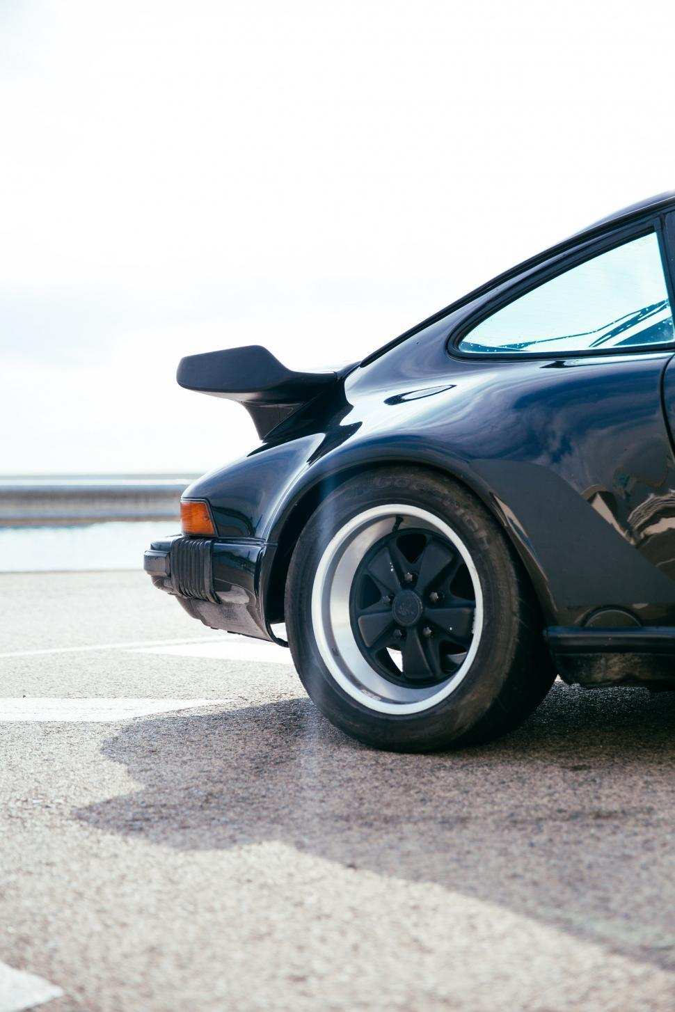 Download Free Stock HD Photo of Side view of a black sports car rear wheel and spoiler Online