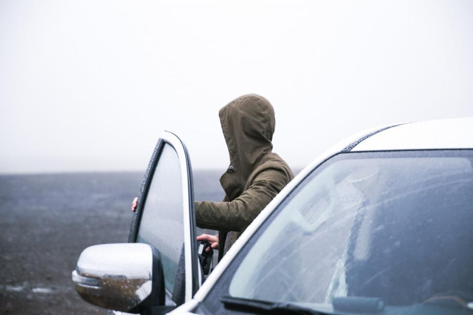 Download Free Stock HD Photo of Hiker in a hooded jacket coming out of car Online