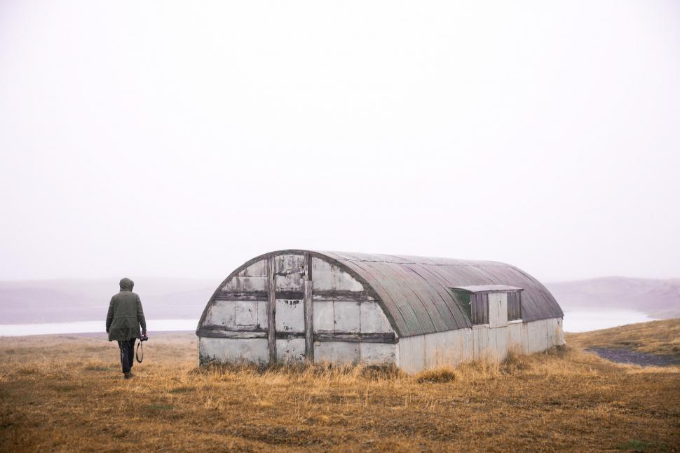 Download Free Stock HD Photo of An abandoned quonset and a hiker Online