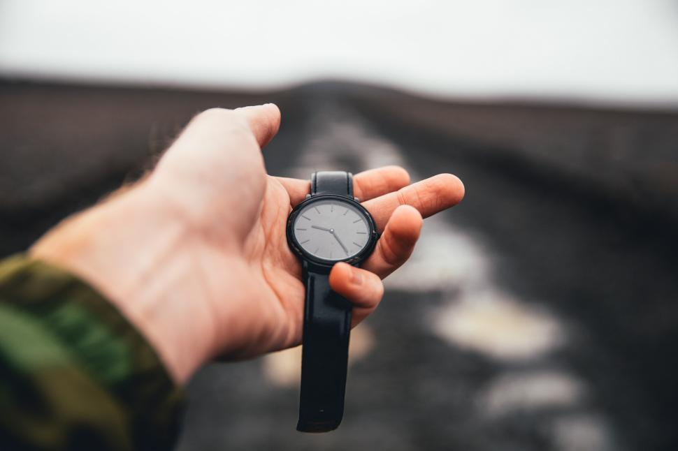 Download Free Stock HD Photo of Wrist watch held in hand over road Online