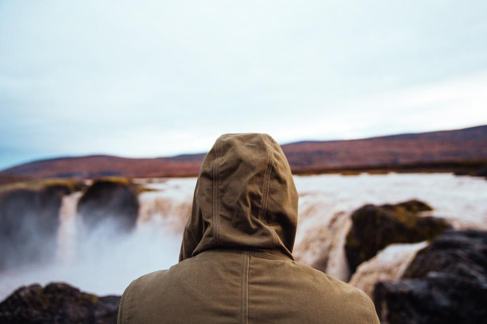 Download Free Stock HD Photo of Hiker in a hooded jacket watching the waterfall Online