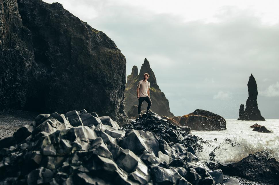 Download Free Stock HD Photo of A young caucasian hiker on volcanic rocks by the sea Online