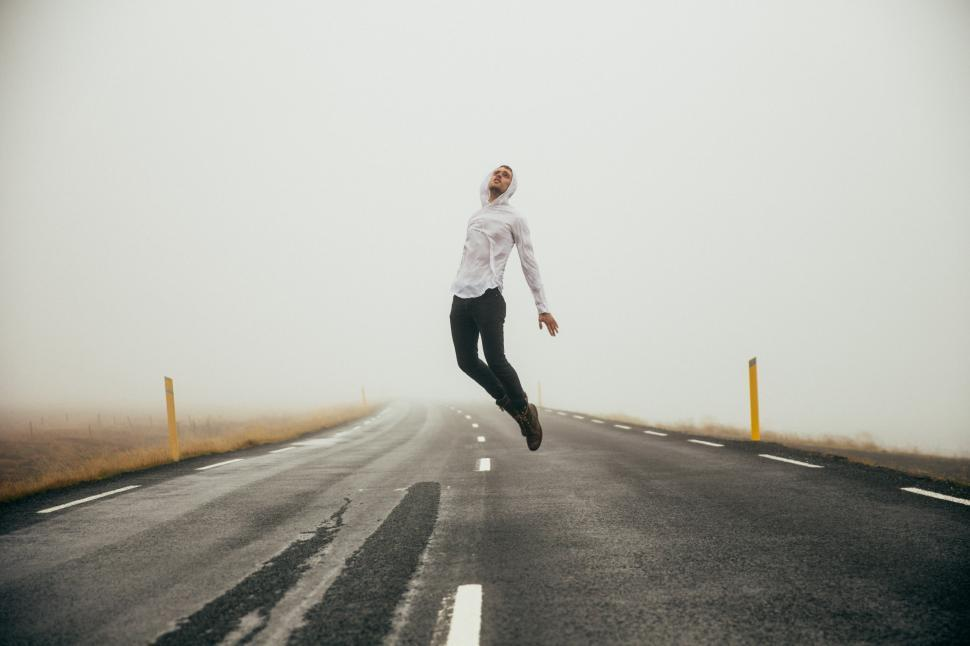 Download Free Stock HD Photo of A young caucasian man jumps on the empty highway Online
