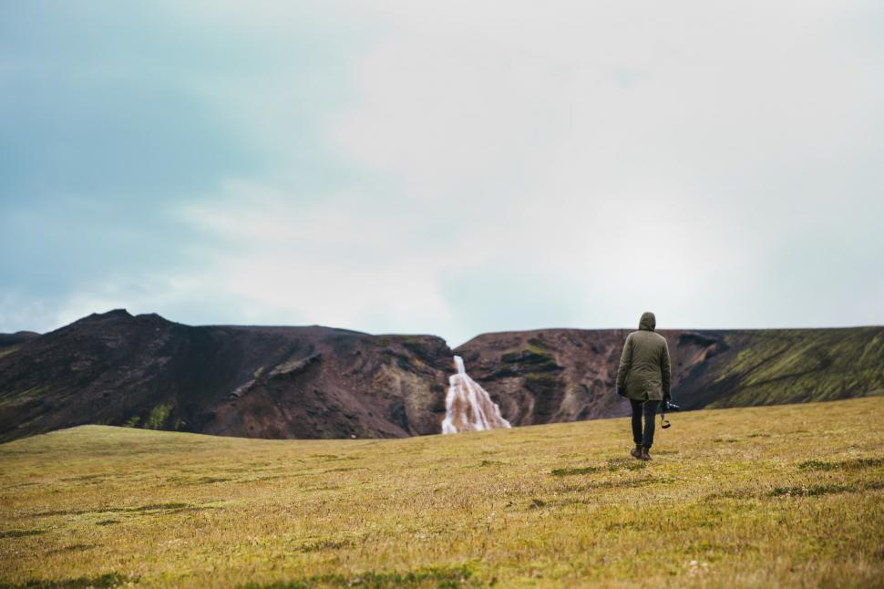 Download Free Stock HD Photo of A hiker on a green field near glacier Online