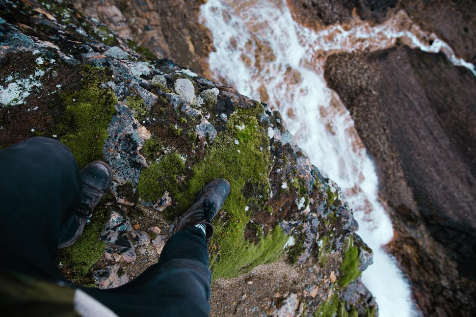 Download Free Stock HD Photo of Feet dangling over moss grown rock edge Online
