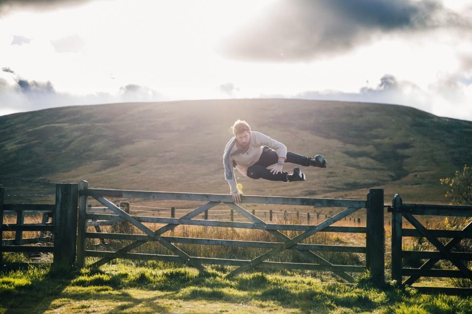 Download Free Stock HD Photo of A young caucasian man jumps over fence Online