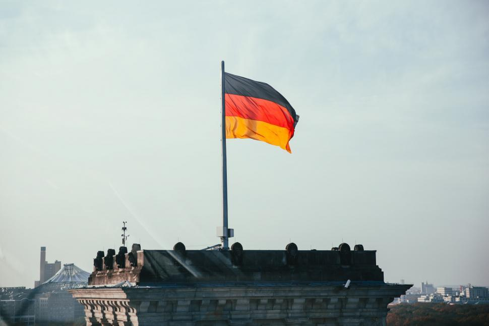 Download Free Stock HD Photo of German flag fluttering on a rooftop Online
