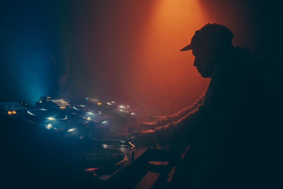 Download Free Stock HD Photo of A DJ operating a music mixing console Online